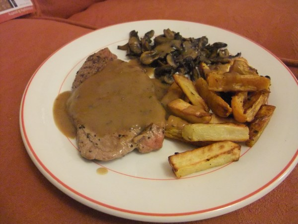Steak with pepper sauce, chips and garlic mushrooms